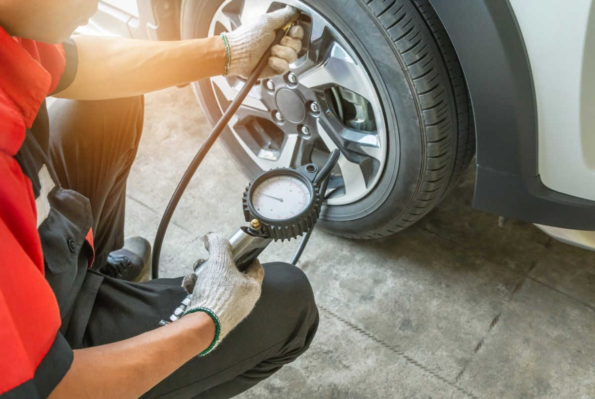 mechanic checking tire pressure on tire