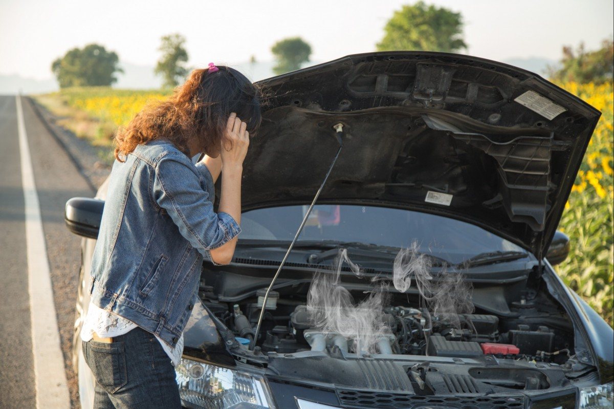 Woman checking out under the hood where steam is coming from